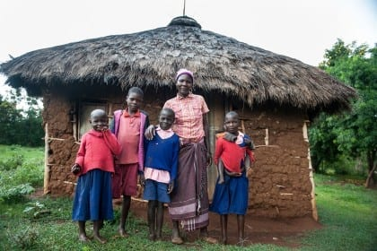 At the home of recipient Rispa Atieno Okoyo in Koga village on 22 October 2014. Rispa used the cash to build this goat pen, she bought 2 cows, and planted maize and beans. Rispa with her children in front of their house.