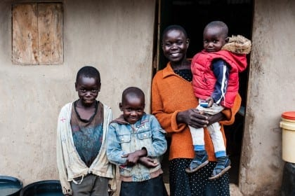 At the home of Caroline Awino Odhiambo in Koga village on 22 October 2014. With the cash transfer from Give Directly, Caroline bought a cow, a sewing machine, put metal sheets on her roof, and paid school fees for two children in primary school. Caroline and her family in front of their house