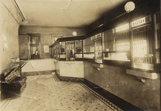 Photo: The First National Bank of Ellendale, ND bank lobby. Employees shown: B.R. Crabtree, behind open counter, Les Briley at the teller window. Picture taken sometime between 1904 and 1909.  CC BY-NC-ND 2.0  Angela Smith