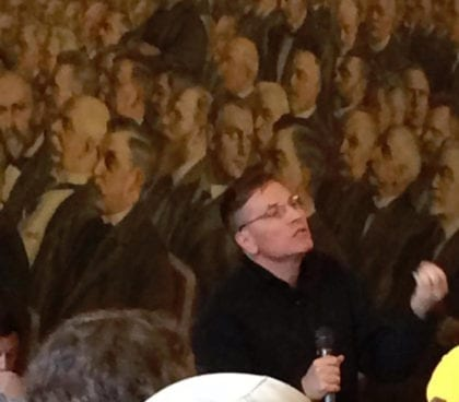 Karl Widerquist in speaking in front of (a painting of) the Danish Parliament
