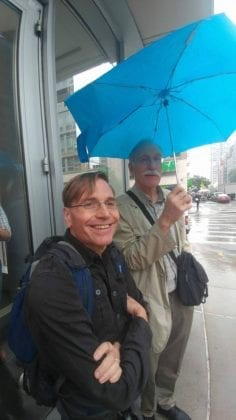 Michael Howard (holding umbrella) and Karl Widerquist in the rain New York in 2017